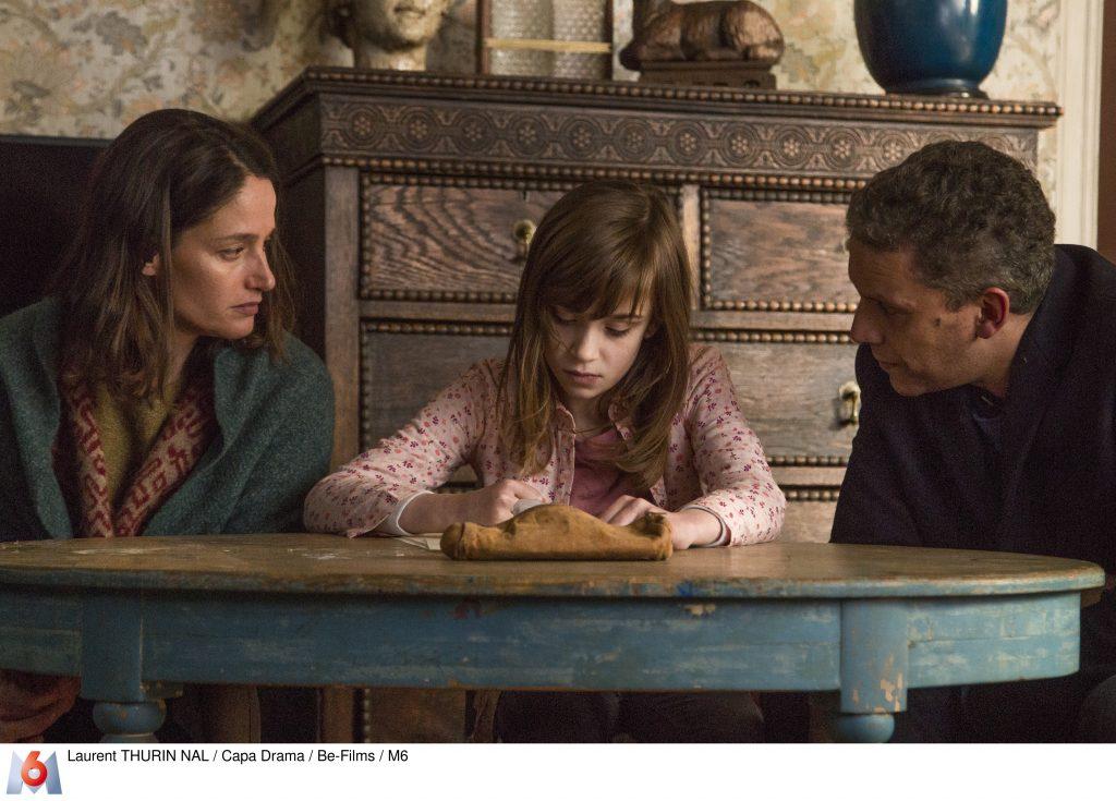Marie Kempf (Marie GILLAIN) et Benoit Belgarde (Sami BOUAJILA) sont assis aux cotes de Madeleine Zelie RIXHON (Zelie RIXHON) qui dessine Visages fermé de Madeleine Zelie RIXHON et attentifs de Marie et Benoit